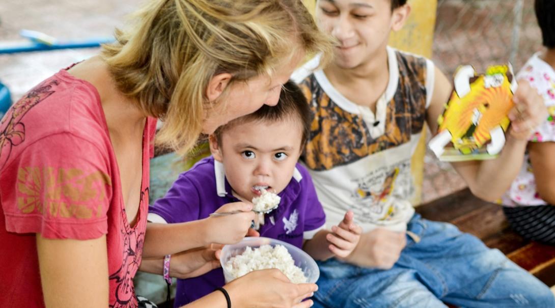 ベトナムで昼ご飯を食べる子供たちを補助するチャイルドケアボランティア